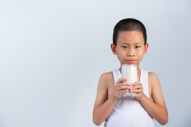 Weinig jongen drinkt glas melk op witte muur. Gratis Foto
