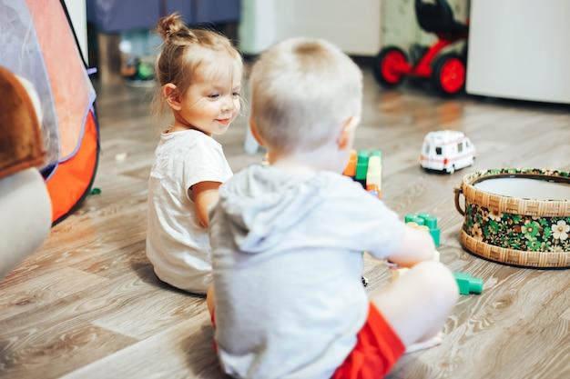 Weinig jongen en meisjes speelspeelgoed thuis Premium Foto