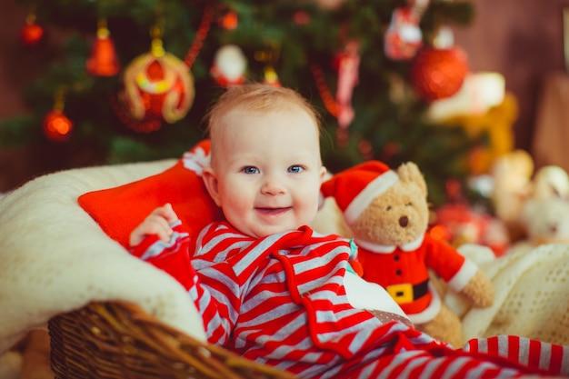 Weinig jongen in gestripte pyjama zit vóór een kerstboom Gratis Foto