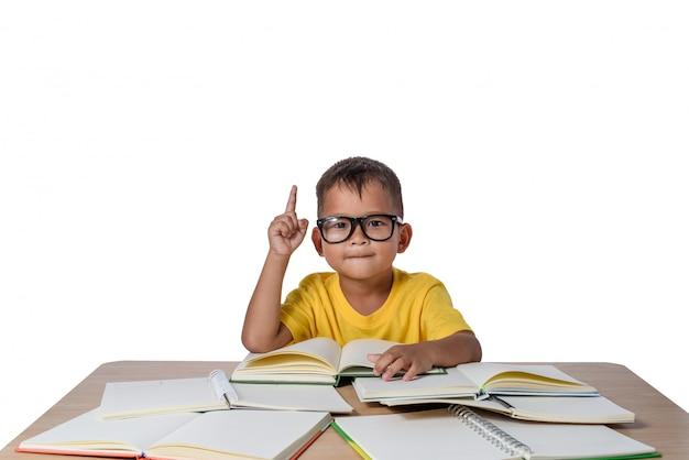 Weinig jongen met gedachte glazen en velenboek op de lijst. terug naar school concept, isolat Premium Foto