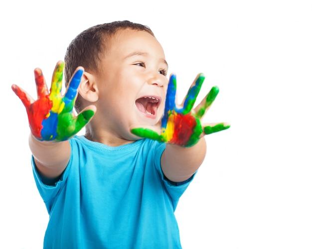 Weinig jongen met handen vol met verf en met open mond Gratis Foto