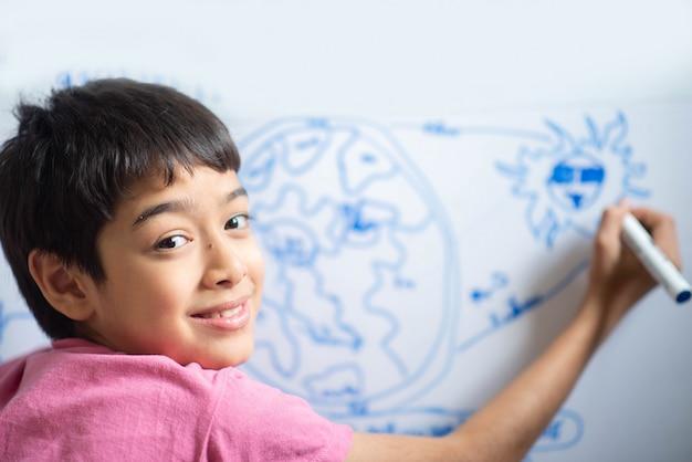 Weinig jongen trekt aarts op het whiteboard in de ruimte Premium Foto