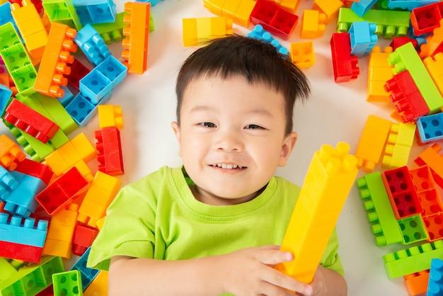 Weinig jongenspeuter die plastic blok kleurrijk met gelukkig spelen Premium Foto
