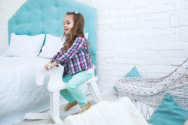 Weinig kind rijdt wit houten paard in blauwe kamer foto gratis