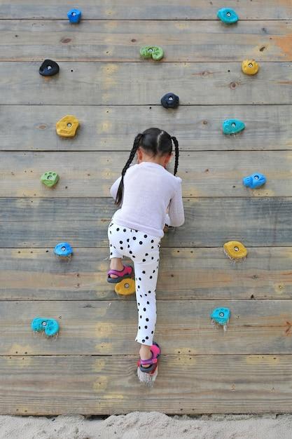 Weinig kindmeisje die bij het vrije beklimmen op de speelplaats houten muur in openlucht proberen. Premium Foto