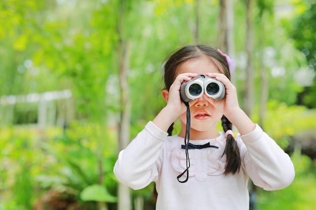 Weinig kindmeisje op een gebied die door verrekijkers in aard kijken openlucht Premium Foto