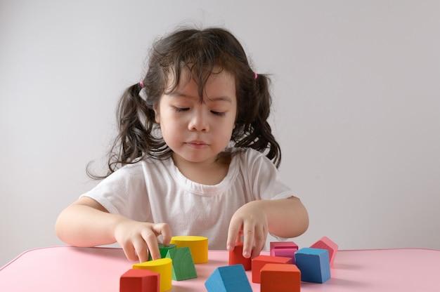 Weinig krullend aziatisch meisje geniet van speel thuis stuk speelgoed. onderwijs concept. Premium Foto