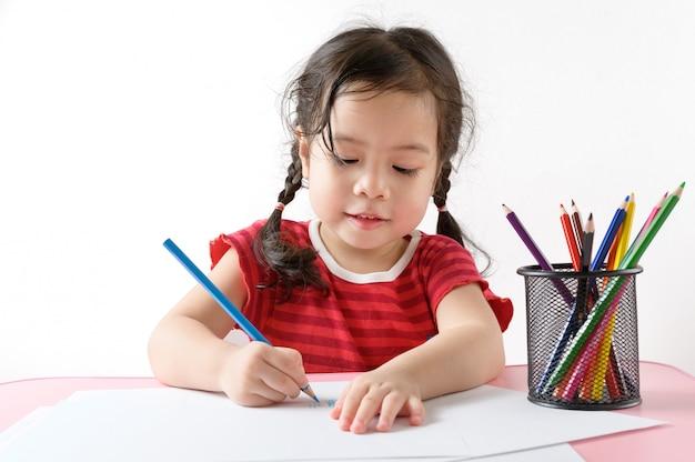 Weinig krullend aziatisch meisje geniet van thuis trekkend. onderwijs concept. Premium Foto