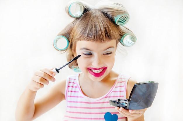 Weinig mode-meisje. meisje maakt haar make-up en manicure. selectieve aandacht. Premium Foto