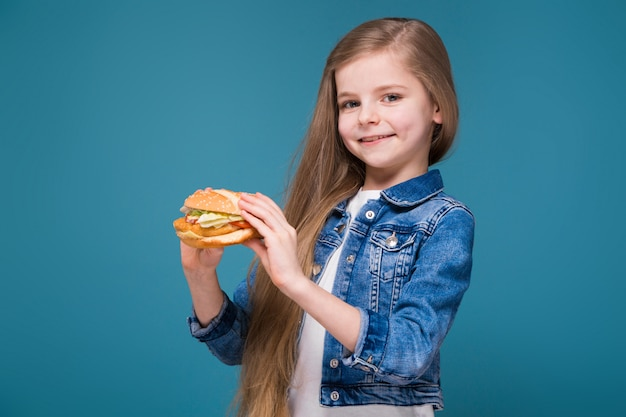 Weinig mooi meisje in het jasje van jean met lang bruin haar houdt een hamburger Premium Foto