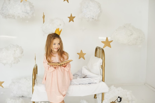 Weinig prinses met een toverstaf op een bed in een wolk op een witte achtergrond Premium Foto