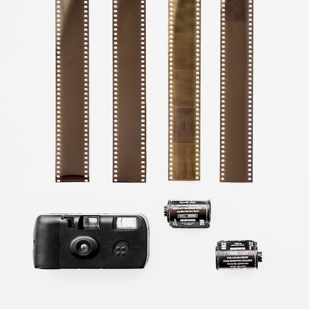 Weinig retro camera dichtbij filmstrippen Gratis Foto