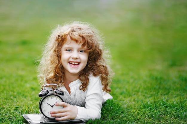 Weinig schoolmeisje die op gazon in het de herfstpark rusten. Premium Foto