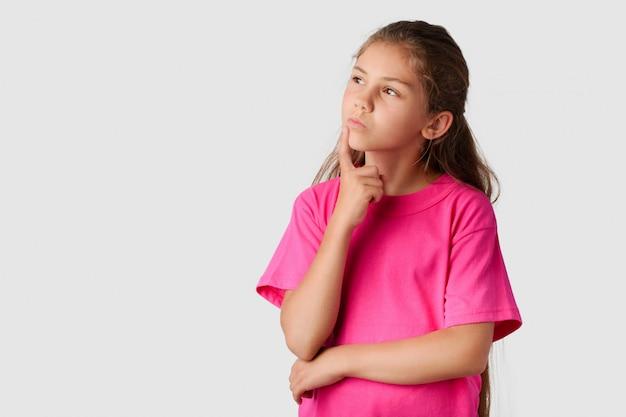 Weinig slim meisje dat aan iets denkt en naar links kijkt. mooi meisje droomt van haar toekomst, besluit wat te doen Premium Foto