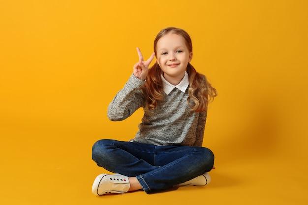 Weinig studentenmeisje zit op de vloer en toont een overwinningsteken. Premium Foto