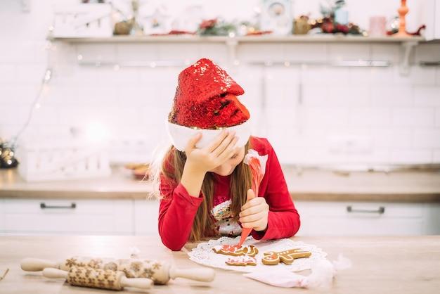 Weinig tienermeisje zit in de keuken en houdt haar hoofd, peperkoekkoekjes met suikerglazuur schilderen Premium Foto