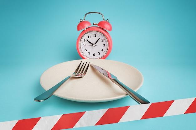 Wekker, bord met bestek en afzetlint. Premium Foto