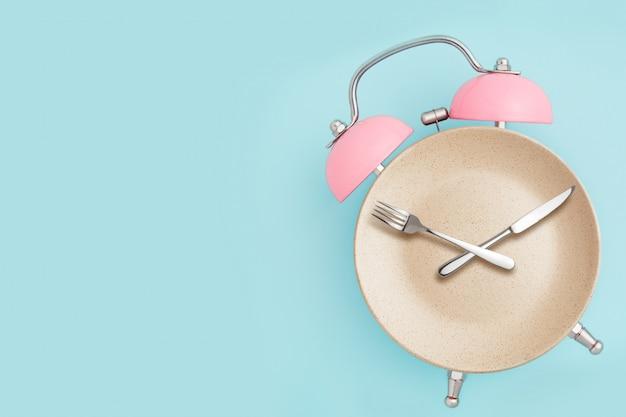 Wekker en bord met bestek. concept van intermitterend vasten, lunch, dieet en gewichtsverlies Premium Foto