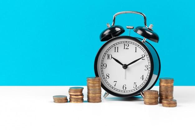Wekker en geldmunten op de tafel. Premium Foto