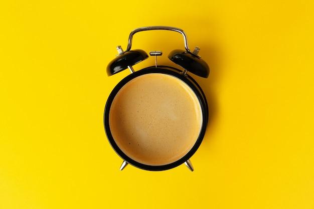 Wekker en koffiekopje op geel Premium Foto