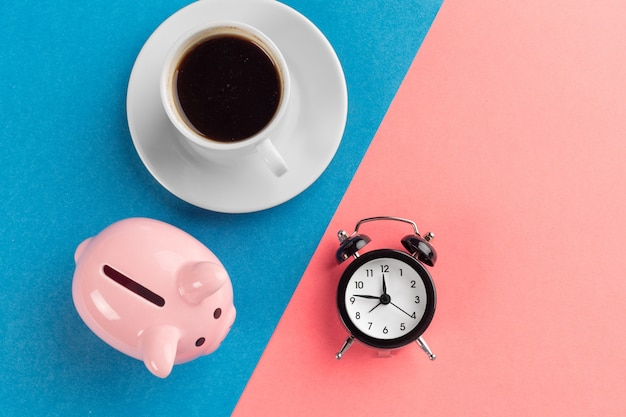 Wekker en spaarvarken op blauw en roze papier Premium Foto