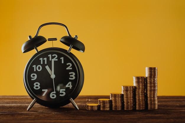 Wekker en stap van munten stapels op werktafel Premium Foto