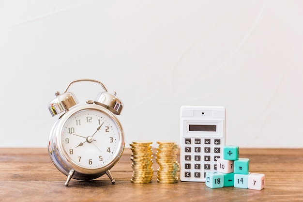Wekker, gestapelde munten, rekenmachine en wiskundige blokken op houten bureau Gratis Foto