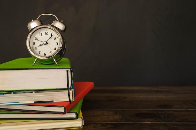 Wekker met boekenstapel op bureau Gratis Foto