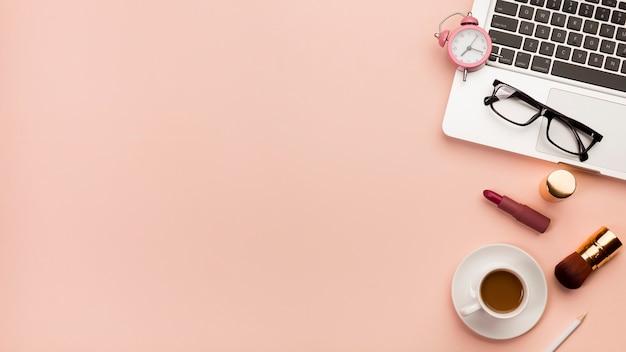Wekker, oogglazen op laptop met koffiekop en make-upproduct tegen perzikachtergrond Gratis Foto