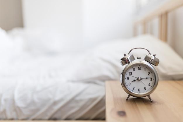 Wekker op houten bureau in de slaapkamer Premium Foto