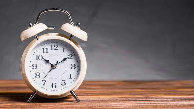 Wekker op houten bureau tegen grijze achtergrond Premium Foto