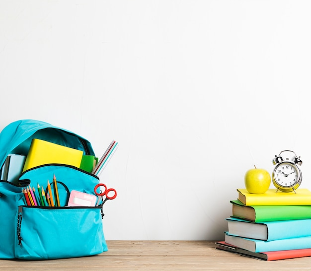 Wekker op stapel boeken en goed ingepakte schooltas met benodigdheden Gratis Foto
