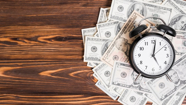 Wekker over de honderd dollar bankbiljetten op houten gestructureerde achtergrond Gratis Foto