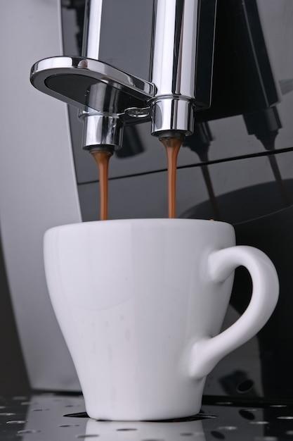Wekkoffie-espresso met gebrande arabica-koffiebonen stroomt onder druk in witte cup Premium Foto