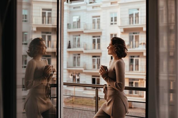 Welgevormde blij meisje cappuccino drinken en stad te kijken. foto van goedgehumeurde dame met kopje thee. Gratis Foto