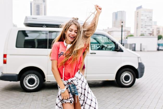 Welgevormde jonge vrouw met lang haar dansen buiten ontspannen met glimlach en gesloten ogen Gratis Foto