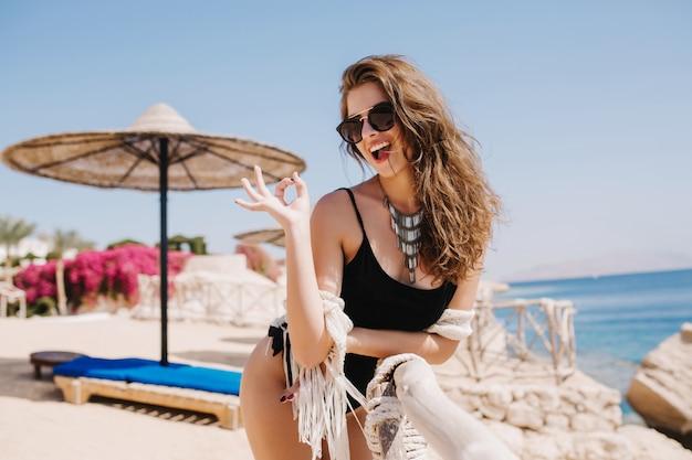 Welgevormde vrolijk meisje in zwarte romper lachen en poseren met goed teken op het strand. aantrekkelijke jonge dame in trendy ketting schattig glimlachen en plezier maken op resort in zomerweekend. Gratis Foto