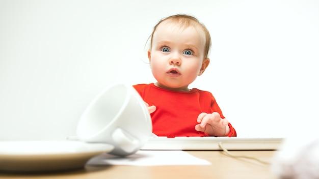 Welke verrast kind babymeisje zit met toetsenbord van moderne computer of laptop in het wit Gratis Foto