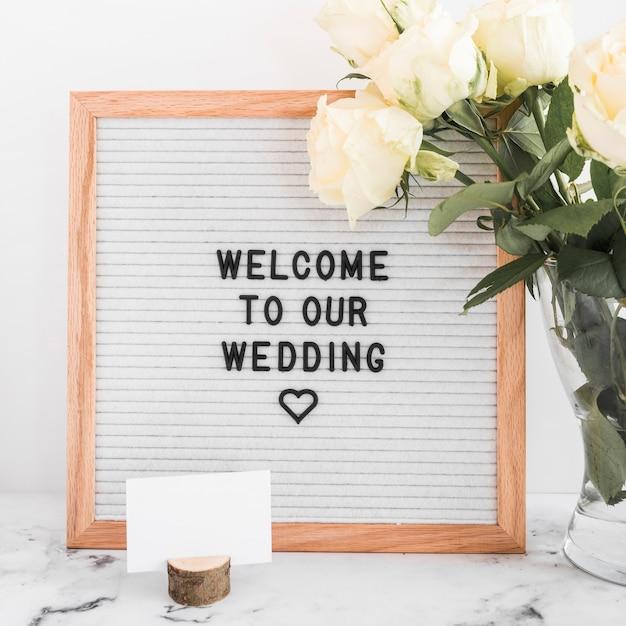 Welkom bij ons huwelijksboodschap op houten frame met leeg visitekaartje en rozen Gratis Foto