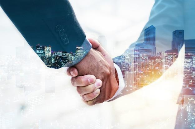 Welkom. dubbele belichting van de handdruk van de zakenpartner Premium Foto