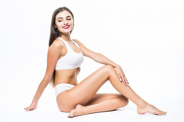 Wellness en beauty concept. mooie slanke vrouw in wit ondergoed zittend op een witte vloer Gratis Foto