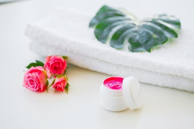 Wellness-producten en cosmetica. kruiden- en minerale huidverzorging. pot met room, witte cosmetische flessen. zonder label. spa set met zeep en witte handdoek Premium Foto