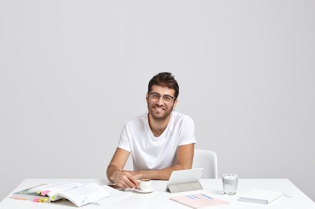 Welvarende glimlachende mannelijke ondernemer in witte t-shirt Gratis Foto