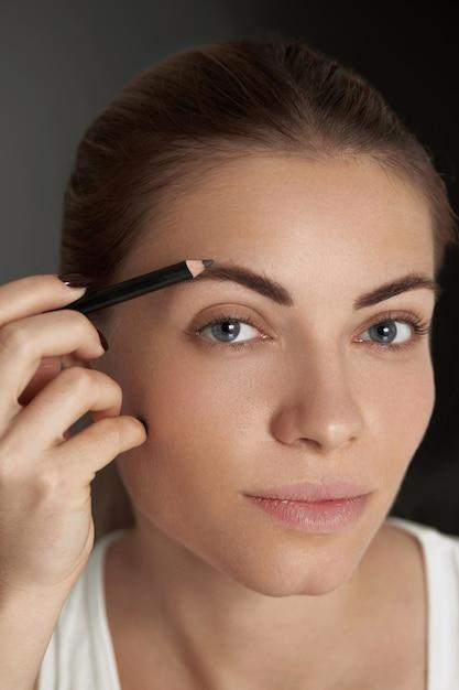 Wenkbrauw make-up. schoonheid model wenkbrauwen vormgeven met wenkbrauwpotlood Premium Foto