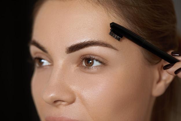 Wenkbrauwcorrectie. vorm. mooie jonge vrouw met perfecte natuurlijke wenkbrauwen en wimpers. Premium Foto