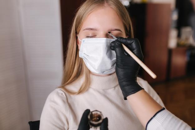 Wenkbrauwmeester in zwart beschermend masker past henna toe op wenkbrauwen voor mooie blonde haarvrouw Premium Foto
