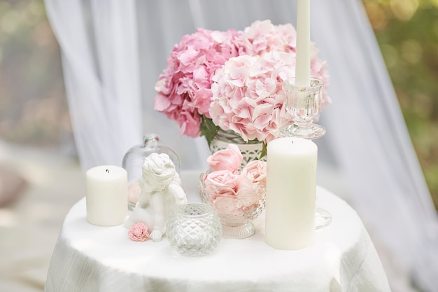 Wenskaart in armoedige chique stijl. hortensia bloemen, engel beeldje, marshmallows, kaarsen op de tafel. Premium Foto
