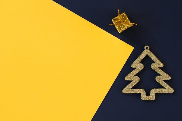 Wenskaart lay-out plat lag, bovenaanzicht. gouden kerstboom en cadeau op de achtergrond van een multi-gekleurde blauwe, gele achtergrond. wenskaart lay-out sjabloon of uw tekstontwerp. kopieer ruimte Premium Foto