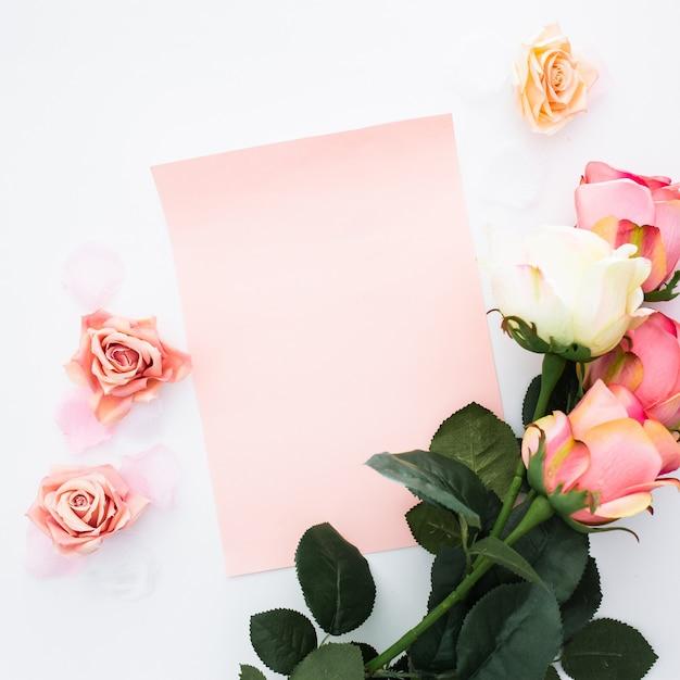 Wenskaart met rozen en bloemblaadjes op wit Gratis Foto