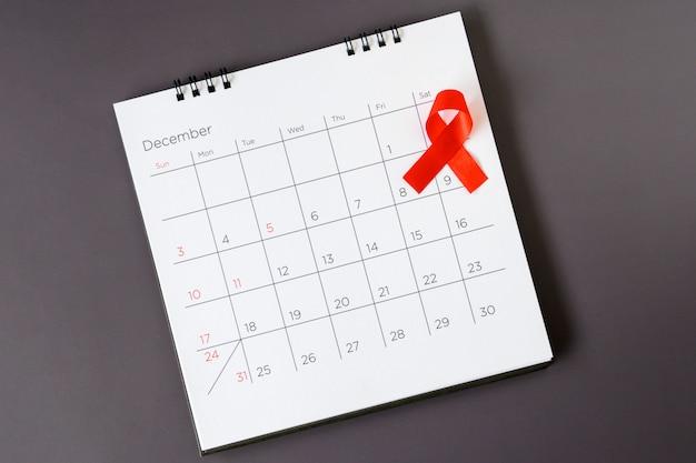 Wereld aidsdag concept, rood lint de datum 1 december Premium Foto
